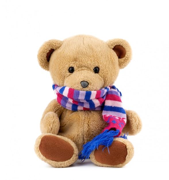 Fofo urso de pelúcia marrom em um cachecol de malha colorido, sentado em um fundo branco Foto Premium