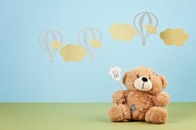 Fofo urso de pelúcia sobre o fundo azul pastel com nuvens e ballons Foto Premium
