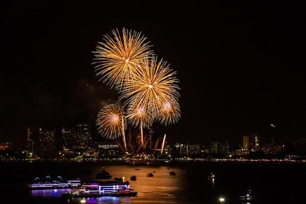 Fogo de artifício colorido sobre fundo de vista cidade à noite para o festival de celebração. Foto Premium