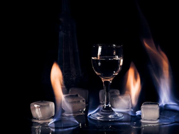 Fogo no copo de vinho, fogo no copo de coquetel, vodka gelo e fogo Foto Premium