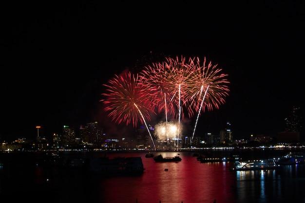 Fogos de artifício cauda longa vermelha na praia e reflexão cor na superfície da água Foto Premium