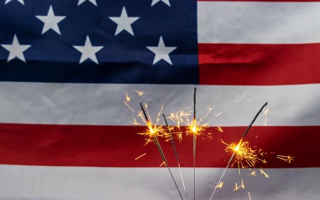 Fogos de artifício cintilantes comemorativos no fundo da bandeira dos eua Foto Premium