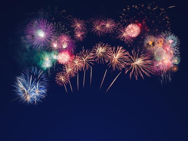 Fogos de artifício coloridos sobre o fundo do céu negro com espaço livre para texto Foto Premium