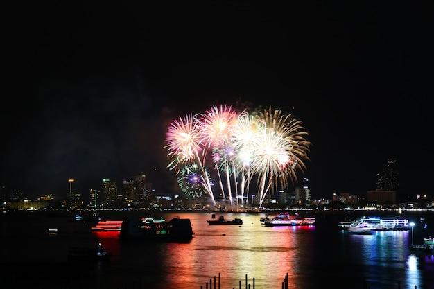 Fogos de artifício multicoloridos na praia e reflexo na superfície da água Foto Premium