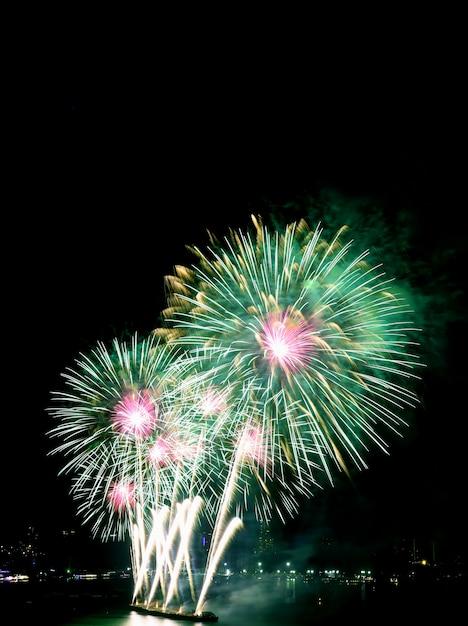 Fogos de artifício verdes e rosa no céu noturno Foto Premium