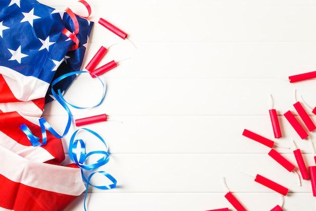 Fogos de artifício vermelhos e fitas azuis com bandeira americana eua na mesa branca Foto gratuita