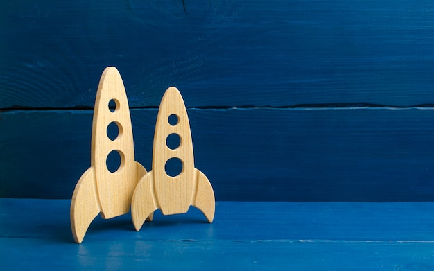 Foguete de espaço de madeira em um fundo azul. o conceito de minimalismo, alta tecnologia Foto Premium