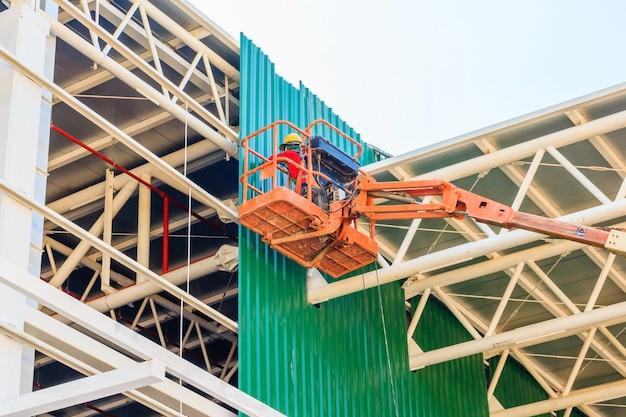 Folha de metal de instalação de trabalhadores de construção no novo edifício Foto Premium