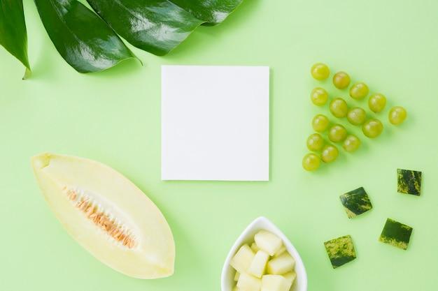 Folha de monstera; uvas; muskmelon em papel branco contra fundo pastel Foto gratuita