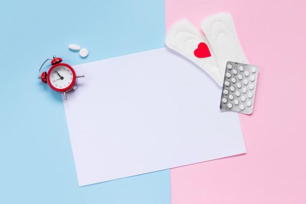Folha de papel branca com almofadas, despertador, pílulas anticoncepcionais hormonais Foto Premium