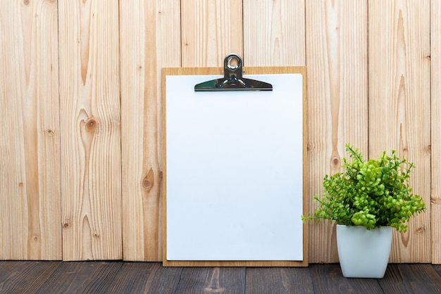 Folha de papel branco em branco da área de transferência com pequena árvore de decoração em vaso branco sobre fundo de madeira Foto Premium