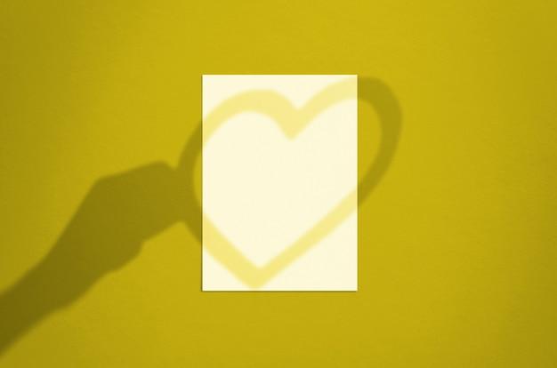 Folha de papel branco vertical em branco de 5 x 7 polegadas com sobreposição de sombra de mão e coração. cartão de dia dos namorados moderno e elegante ou simulação de convite de casamento. Foto Premium