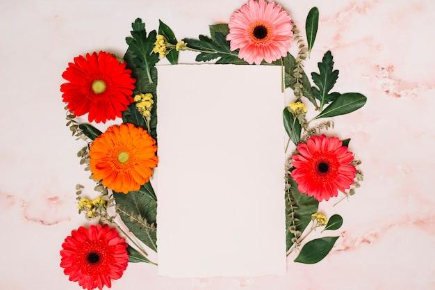 Folha de papel com flores brilhantes na mesa Foto gratuita