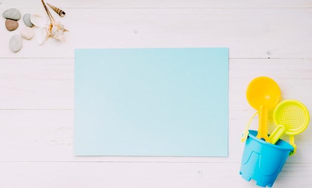 Folha de papel em branco com objetos de praia na luz de fundo Foto gratuita