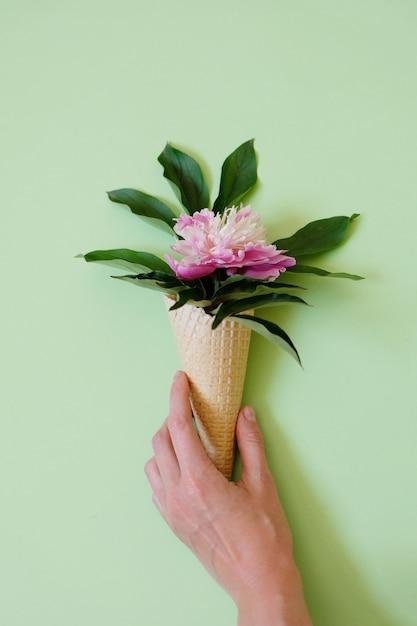 Folha de peônia em um cone de waffle. conceito de verão. Foto Premium