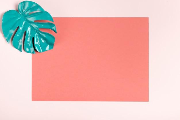 Folha de turquesa na maquete de fundo rosa Foto gratuita