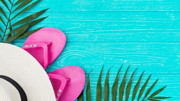 Folhagem de planta verde fresco perto de flip-flops e chapéu Foto gratuita