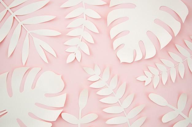 Folhas artificiais estilo de corte de papel com fundo rosa Foto gratuita