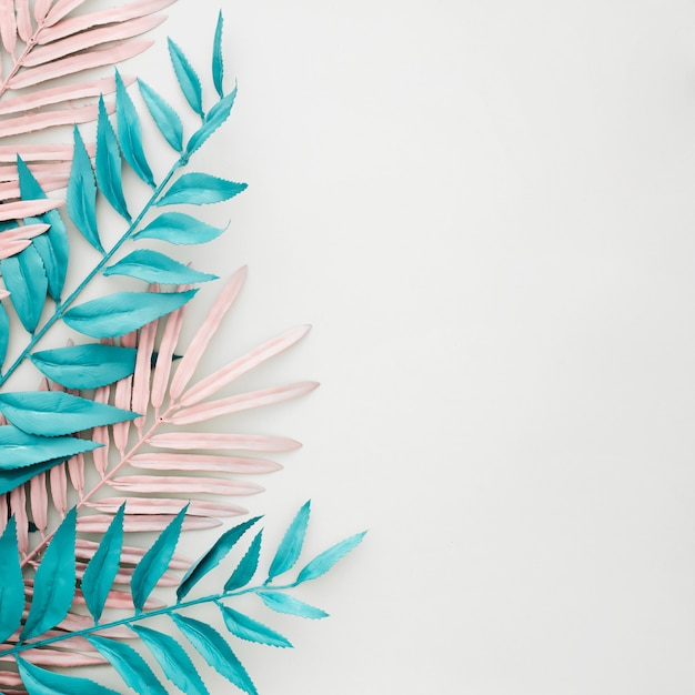 Folhas azuis e rosa tingidas em fundo branco com copyspace Foto gratuita