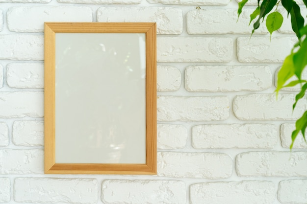 Folhas da planta da casa contra a parede de tijolos brancos com espaço de cópia Foto Premium
