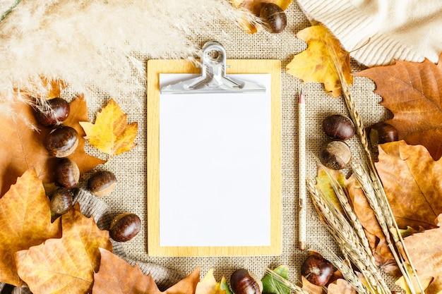 Folhas de bordo do outono, lista do livro branco, lápis e castanhas encontrando-se em um marrom. Foto Premium