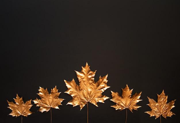 Folhas de bordo dourado sobre um fundo preto Foto Premium