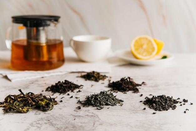 Folhas de chá de ervas secas com chá e limão no pano de fundo texturizado em mármore Foto gratuita