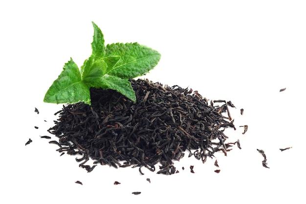 Folhas de chá preto secas e hortelã isoladas em branco Foto Premium
