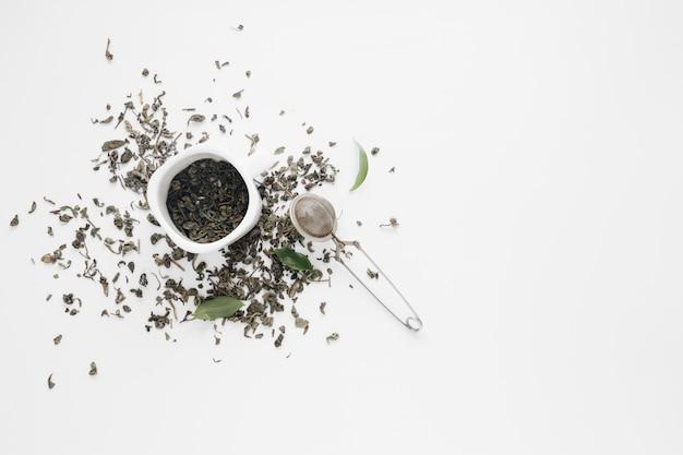 Folhas de chá seco com folhas de café e coador de chá no pano de fundo branco Foto gratuita