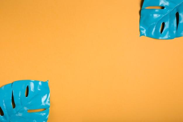 Folhas de luz azul em fundo laranja com espaço de cópia Foto gratuita