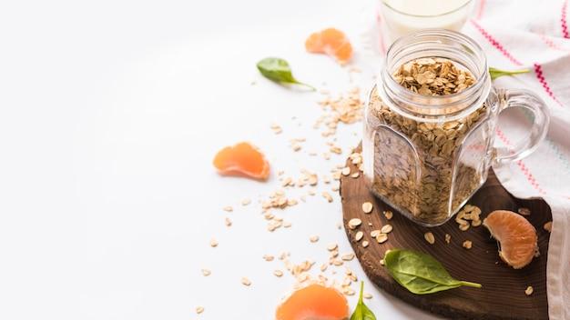 Folhas de manjericão; pote de aveia; fatias de laranja e guardanapo isolado sobre fundo branco Foto gratuita