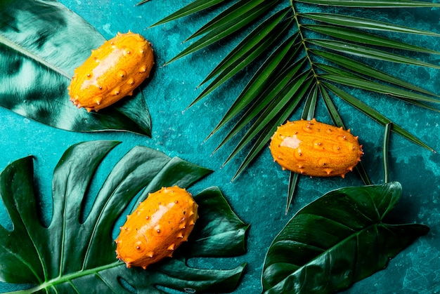 Folhas de maracujá tropical kiwano maracujá em tigela verde em turquesa com palmeira tropical folhas. vista do topo. tropical Foto Premium
