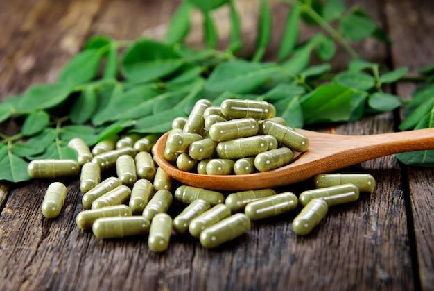 Folhas de moringa e cápsulas (ervas para a saúde) Foto Premium