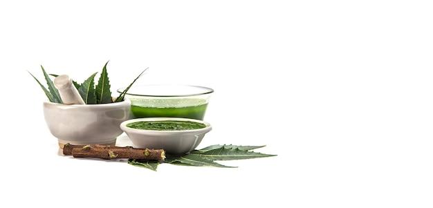 Folhas de nim medicinal em almofariz e pilão com pasta de nim, suco e galhos na superfície branca Foto Premium