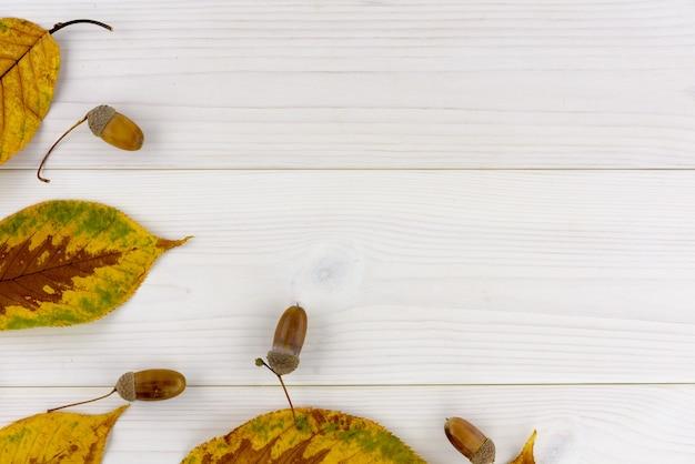Folhas de outono amarelas e bolota em uma mesa de madeira branca Foto Premium