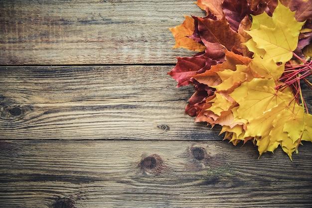 Folhas de outono amarelas sobre fundo de madeira com copyspace Foto Premium