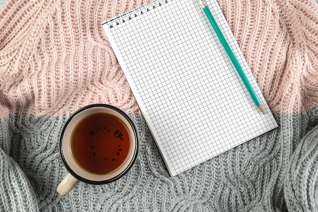 Folhas de outono amarelas, uma xícara de chá e um caderno em uma blusa texturizada Foto Premium