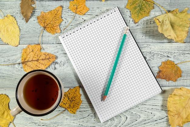Folhas de outono amarelas, uma xícara de chá e um caderno sobre um fundo claro de madeira velho Foto Premium