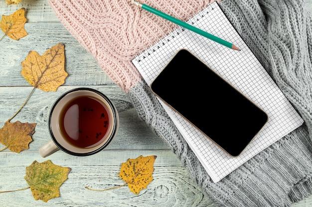 Folhas de outono amarelas, uma xícara de chá e um smartphone em um fundo de madeira velho Foto Premium