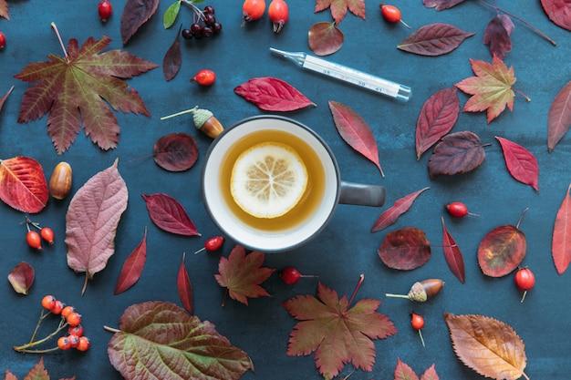 Folhas de outono coloridas, bagas de rosa mosqueta madura com uma xícara de chá quente com limão, termômetro de mercúrio com alta temperatura sobre fundo azul, plana leigos Foto Premium