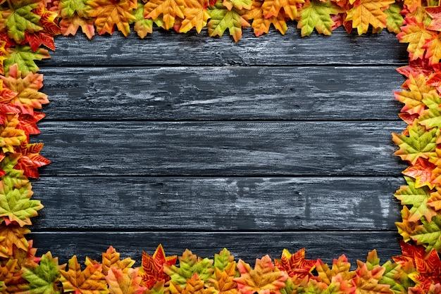 Folhas de outono em um fundo preto de mesa de madeira. ação de graças, conceito de halloween Foto Premium