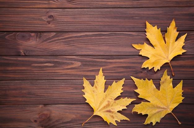 Folhas de outono laranja na mesa marrom. dia de ação de graças Foto Premium