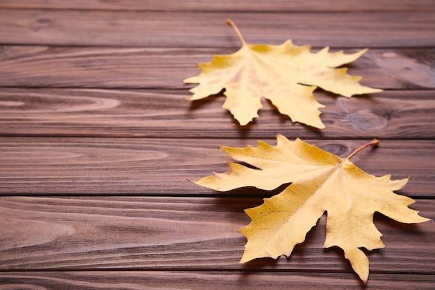 Folhas de outono vermelhas e laranja na mesa marrom Foto Premium
