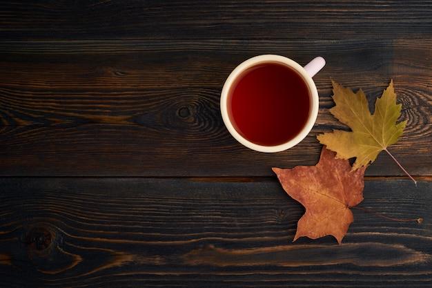 Folhas de outono, xícara de chá, uma mesa de madeira escura. vida de outono aconchegante ainda Foto Premium