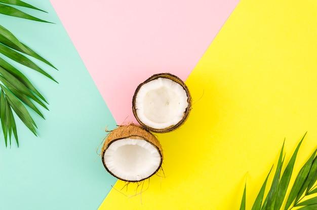 Folhas de palmeira com cocos na mesa brilhante Foto gratuita