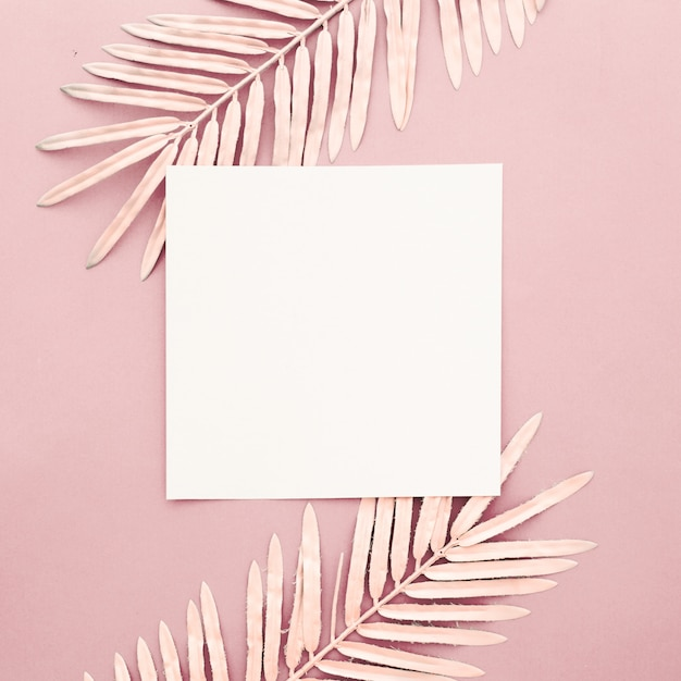 Folhas de palmeira rosa com moldura em branco sobre fundo rosa Foto gratuita