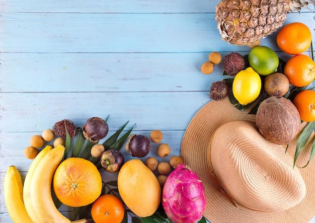 Folhas de palmeira tropical, chapéu, muitas frutas no fundo de madeira azul. Foto Premium