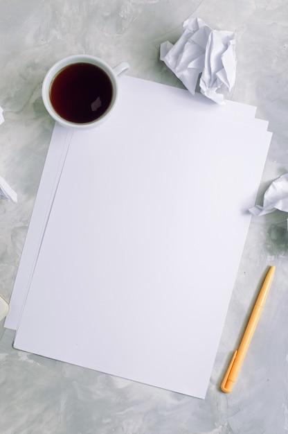 Folhas de papel vazio e papel amassado sobre fundo de concreto: vista de cima, copie o espaço Foto Premium