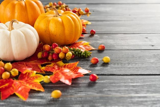Folhas de plátano e abóbora do outono no fundo de madeira velho. conceito de dia de ação de graças. Foto Premium