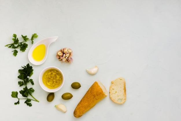 Folhas de salsa; azeite; alho e pão no pano de fundo texturizado branco Foto gratuita